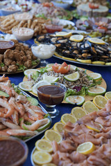 Selection of cold bits, sea food, meat, salads and sauces at a buffet bar, or self-service restaurant. Assorted cold food displayed on individual plates at a wedding, birthday party or banquet.