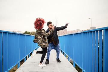 Stylish black couple walking on bridge