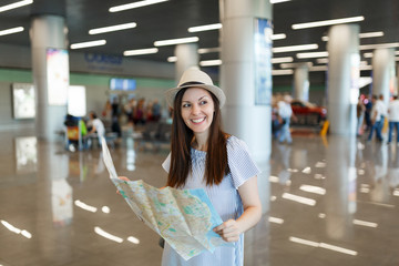 Young smiling traveler tourist woman in hat holding paper map, searching route while waiting in lobby hall at international airport. Passenger traveling abroad on weekends getaway. Air flight concept.