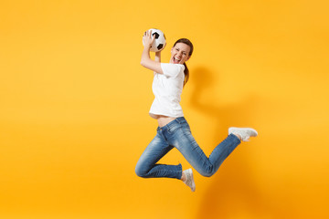 Young fun expressive European woman football fan jumping in air, cheer up support team, holding soccer ball isolated on yellow background. Sport, play football, cheer, fans people lifestyle concept.