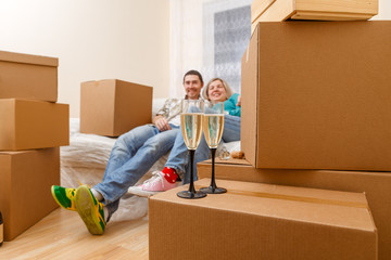 Photo of man and woman sitting on sofa among cardboard boxes with two wine glasses