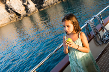 cute girl is eating her apple at boat