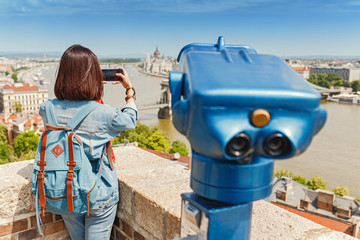 Young female tourist taking photos of the old town of Budapest. Travel and view point concept