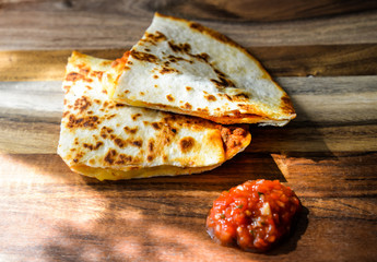 Two pieces of hot tasty quesadilla with salsa sauce on a wooden cutting board for cafe, shop, menu, prints, market, advertising. Freshly baked tortillas with cheese and meat close up. Cake, tortilla.