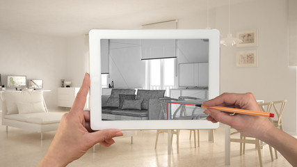 Hands holding and drawing on tablet showing modern living room CAD sketch. Real finished minimalist white project in the background, architecture interior design presentation