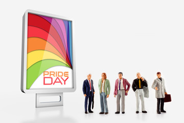 miniature people - A group of men standing in front a board about the Gay Pride