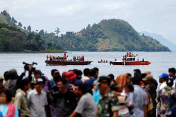 Rescue team members during an operation, as relatives of the missing passengers after a ferry sank earlier this week in Lake Toba, are waiting at Tigaras port in Simalungun