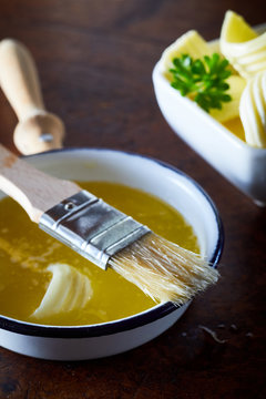 Bowl of melted butter with a basting brush