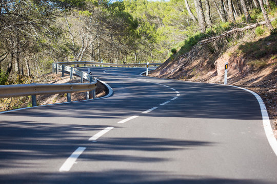 sinuous asphalt road through highlands covered with forests
