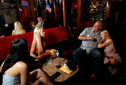 Dennis Hof sits in the parlor with Misty Matrix his girlfriend and a legal prostitute, and other working girls at his Moonlite BunnyRanch legal brothel n Mound House