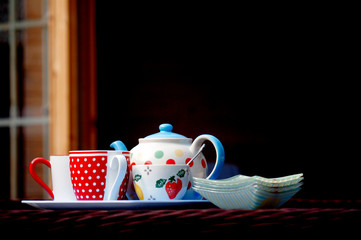 A pot of tea, with a dotty mug and sugar bowl, ready for tea in the sun.