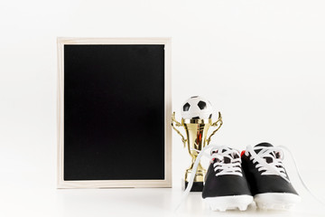 Football composition with leaning slate next to shoes