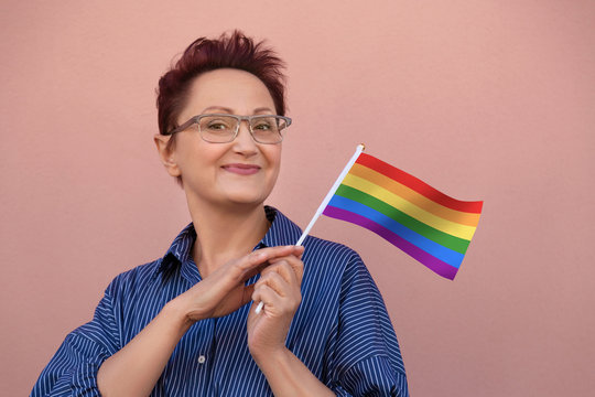 LGBT flag. Woman holding rainbow flag. Nice portrait of middle aged lady 40 50 years old with a flag over pink wall background.