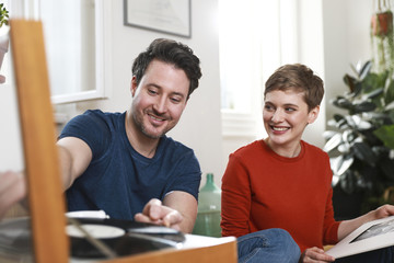 Couple sitting at home, listening to old records