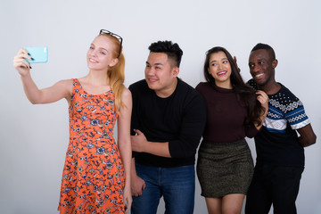 Happy diverse group of multi ethnic friends smiling while taking