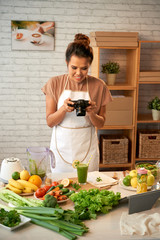 Attractive middle-aged food blogger wearing apron taking picture of healthy smoothie while standing at modern kitchen