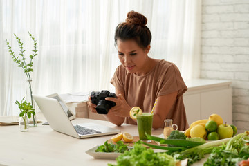 Portrait shot of pretty Asian food blogger looking through photos on modern camera while working on her vlog at home
