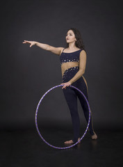 Gymnastic exercises with hula-Hoop girl performs circus performer in an artistic costume.