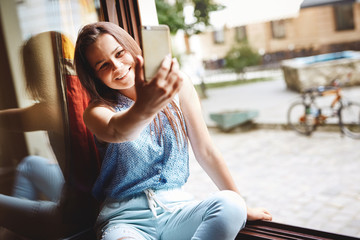 young girl in coffeeshop using mobile phone