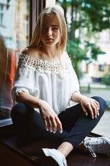 young girl in coffeeshop sitting on the window sill