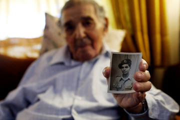 Retired senior civil servant Ram Haviv, 93, holds a photograph of himself during his service in the British army between 1943-1946, in his home in Jerusalem