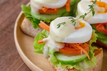 Open faced sandwich with toast and fresh vegetable and boil egg top with salad dressing or mayonnaise on wooden plate. Delicious breakfast for family on wood table. Homemade and healthy food concept.