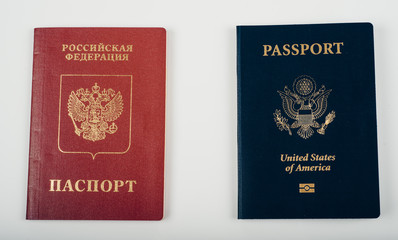 Red Passport of Russia (Russian Federation) - Cyrillic labels and Blue passpost of USA (United states of America) on white background.