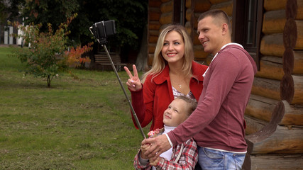 Family taking a selfie in the countryside on an autumn day. Against the background of a country house.