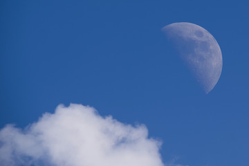Moon closeup on blue sky and clouds background