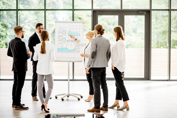 A group of business people standing together during the conference with flip chart at the modern office