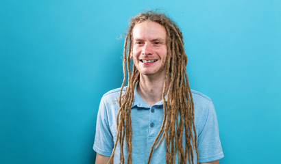 Happy young man with dreadlocks on a solid background