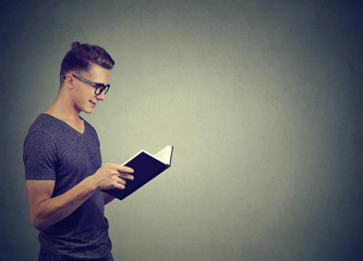 Smart man in glasses reading book