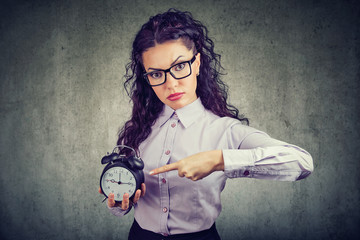 Serious woman pointing at alarm clock