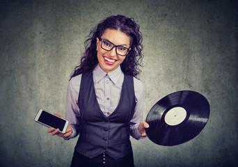 happy woman in glasses choosing between vinyl disk and smartphone