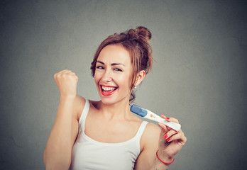 Excited woman with positive pregnancy test
