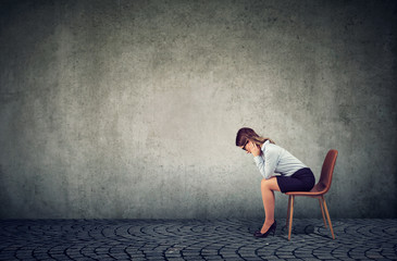 Depressed business woman sitting on chair and looking down