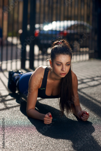 9ae92576b2 Young beautiful tanned brunette woman doing plank outdoors at workout  space. Sport concept. Fitness bikini girl training or doing exercises.