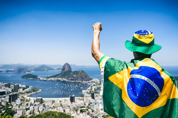Patriotic Brazilian fan wrapped in flag holding up fist pump at Sugarloaf Mountain Botafogo view Rio de Janeiro. Fototapete