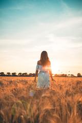 Bellissima ragazza con vestito bianco in mezzo a un infinito campo di grano al tramonto.