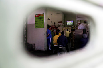 Workers watch the broadcast of the World Cup Group E soccer match between Brazil and Costa Rica inside a closed store in Sao Paulo