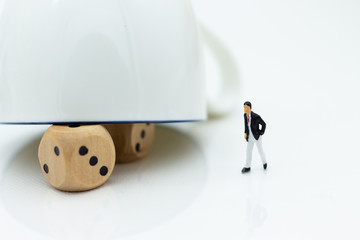 Miniature people: Businessman with a glass with dice inside, risky investment. Image use for business concept.