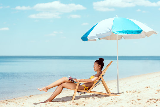 side view of african american woman reading magazine and relaxing on deck chair under beach umbrella in front sea