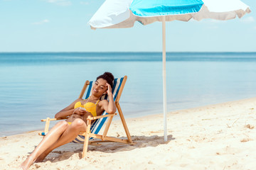 young african american woman relaxing on deck chair and listening music in earphones with smartphone under beach umbrella in front of sea