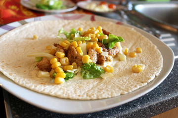 Healthy tortilla with meat, salad, cheese and corn