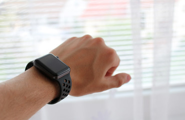 Man's hand with black smart watch in office