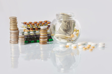 Packs of medicine blisters with pills, dollar bills, packs of coins on glass table. Some pills laying in glass pot, scattered pills on a table Medical prescription for health Cost of the healthy life
