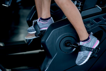 close up woman feet ride bicycle machine in gym health ideas concept