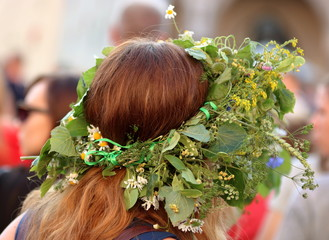 Obraz Głowa rudowłosej kobiety w kwietnym wianku na głowie, tradycja nocy świętojańskiej, tradycja ludowa - fototapety do salonu