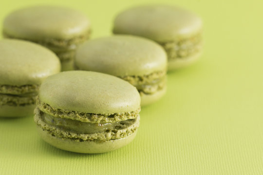 Green French Macarons on a Green Background
