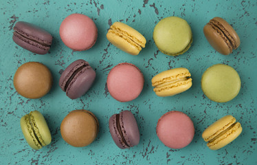 A Variety of French Macarons Flavors on a Textured Turquoise Background